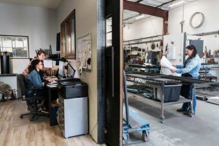 Two women at a desk in office area of a metal workshop.