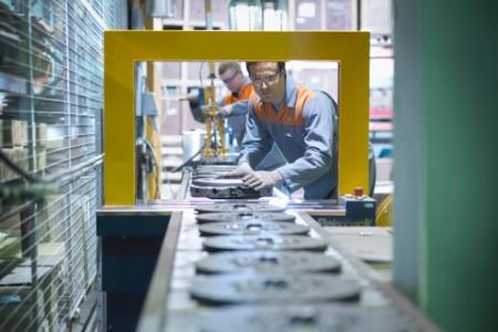 Lucrători pe linia de producție la o fabrică de ambreiaje
