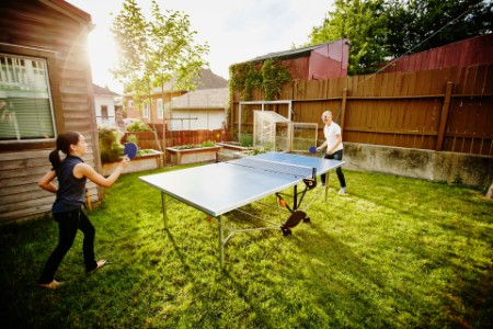 Young daughter and father playing ping pong