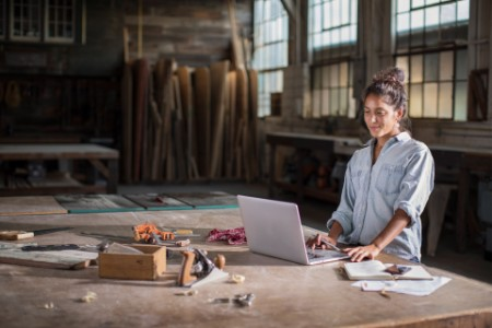 Young mixed race woman stands at her sturdy wooden worktable