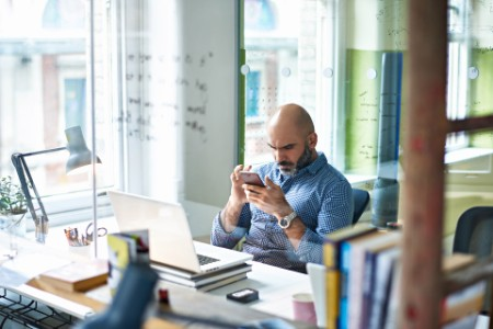 businessman using mobile phone at desk in modern office
