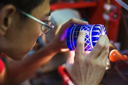 Craftsman inspecting blue glass cut glass cup