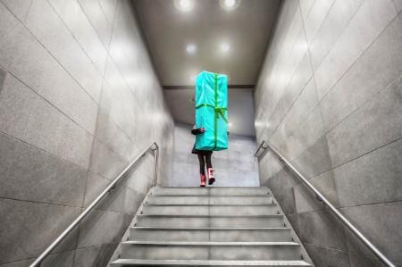 Chica corriendo por las escaleras con un gran regalo