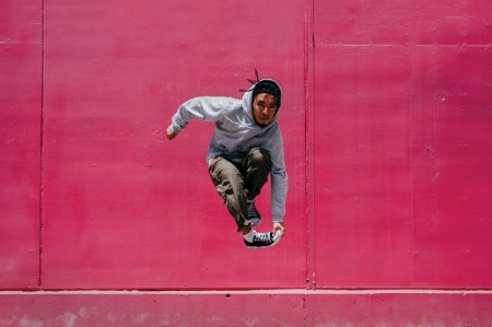 Man jumping near pink wall street