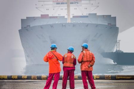 Tres trabajadores esperando que llegue el barco