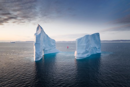 boat with red sail between icebergs in Greenland