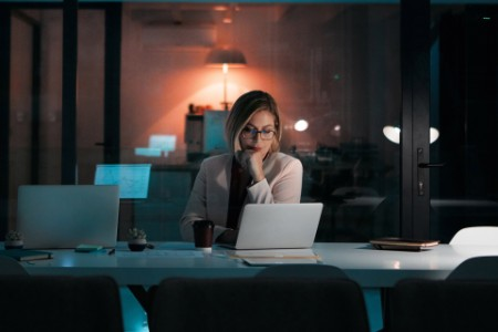 Businesswoman using a laptop at her desk during a late night at work