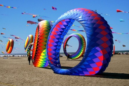 colorful ring kites at sandy beach against clear sky on sunny day