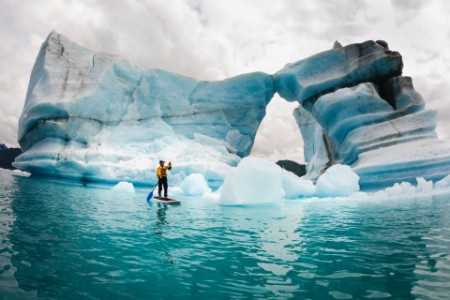 man stand up paddle board hole melted iceberg Alaska