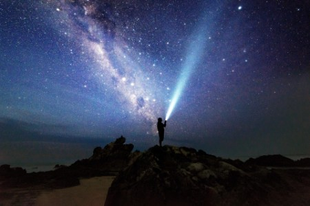 Man with torch and milkyway at sawarna beach bayah indonesia
