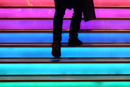Person walking up colorful staircase
