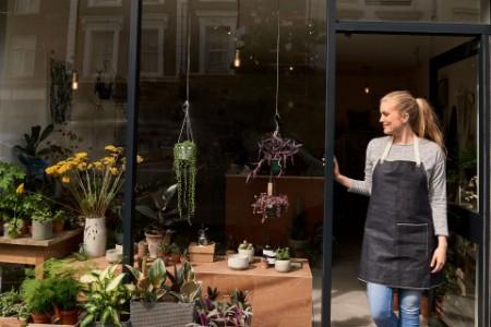Shop owner stands in doorway of florists