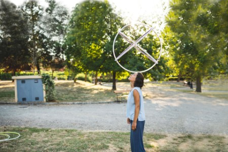 woman balancing hula hoop on her head at the park