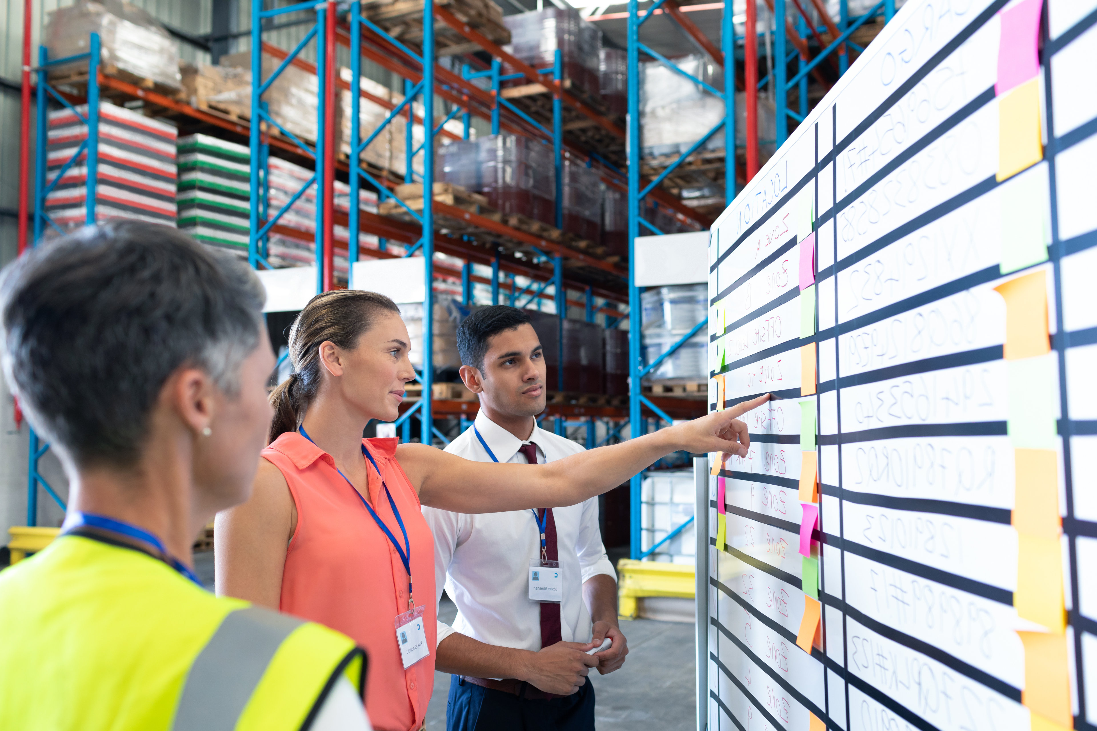 Staff discussing details against a whiteboard in a warehouse