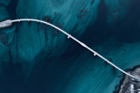 aerial shot of a bridge over sea strait near tromso sommaroy norway