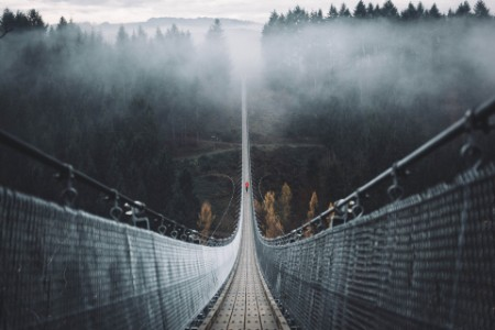 man walking over suspension bridge in the fog