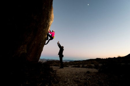 Female rock climber boulders at sunset spotted by her friend