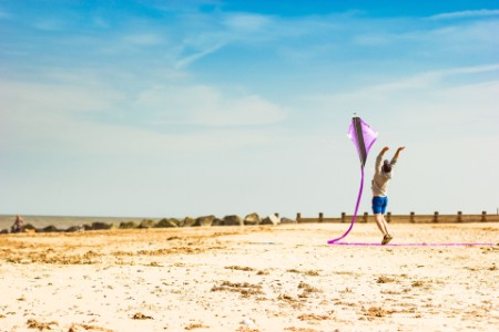 A man launching a kite on the beach
