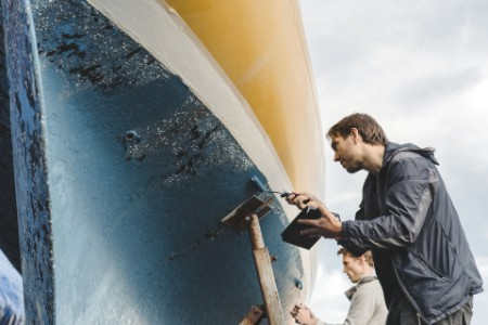 Two men painting a fishing boat