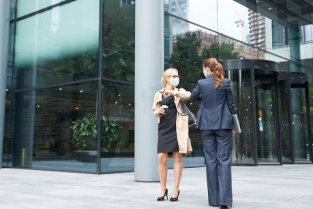 Business people wearing face mask greeting with elbow