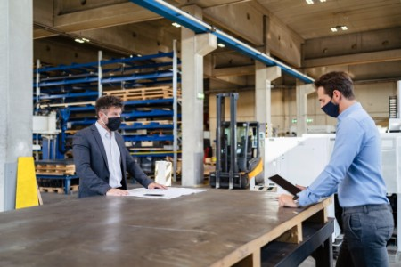 Businessman standing at social distance with colleague in factory