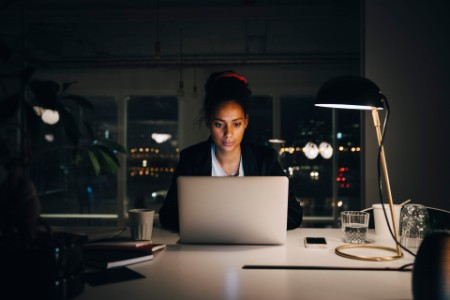 Businesswoman working late while using laptop