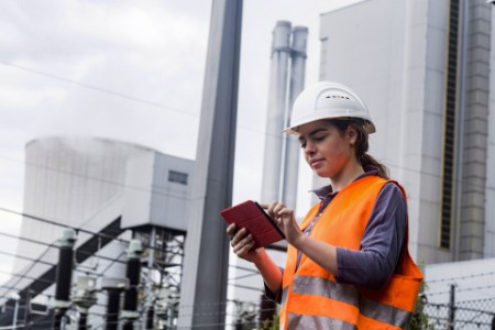 Female worker using tablet at power plant