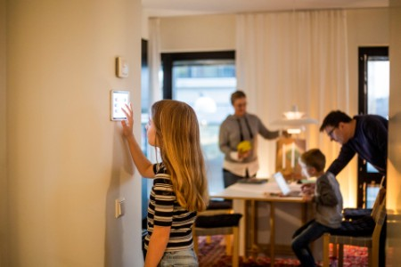 Girl using digital tablet on wall with family in background at smart home