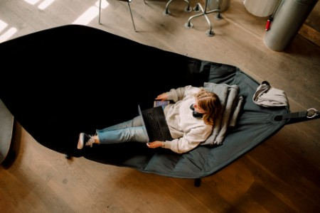 High angle view of woman on hammock with laptop