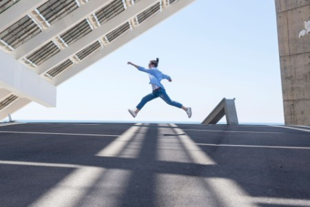 Man leaping under solar panels