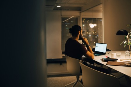 man working at laptop alone in office