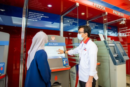 Member of teenager staff shows customer an i kiosk
