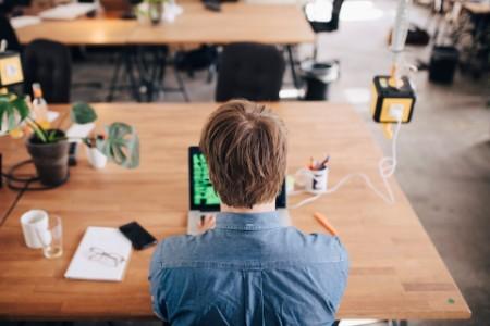 Rear view of man working on laptop in open office