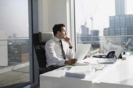 Thoughtful businessman with paperwork in sunny, modern, urban office