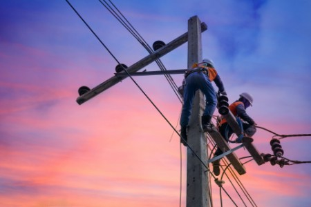 Two electrical lineman repairing a power pole