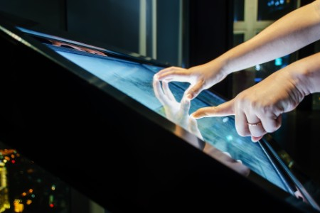 Two people reaching out and touching an interactive screen