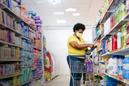 Woman in face mask choosing cleaning products in supermarket