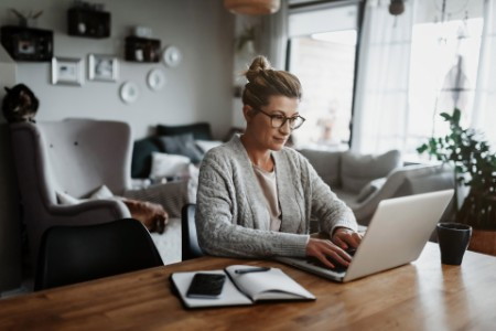 Woman using laptop on table while sitting