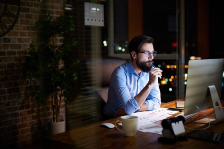 Young businessman looking at computer on office desk at night