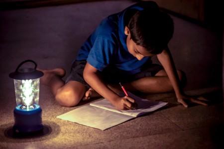Menino indiano estudando sob a luz da lâmpada