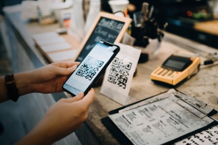 Customer scanning QR code making contactless payment in a cafe