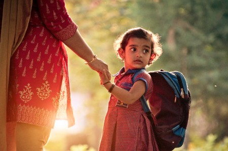 Menina caminhando para a escola com a mãe