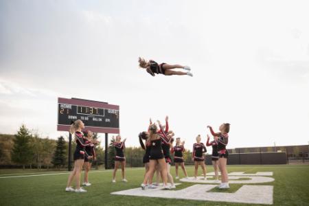 High school cheer-leading team performing on football field