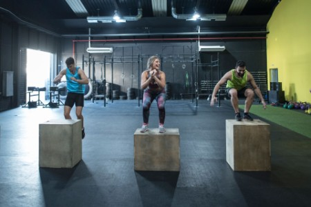 Three people in a gym on jumping blocks
