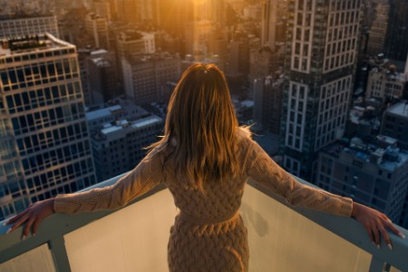 Woman balcony new york sunset
