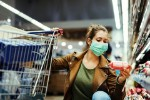 Woman buying groceries wearing face mask in the supermarket