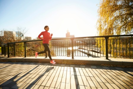 EY woman jogging over bridge on sunny morning