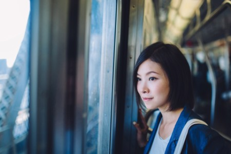 Woman on subway looking out at city