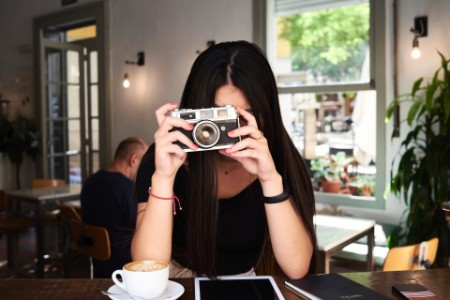 Woman taking picture camera coffee shop