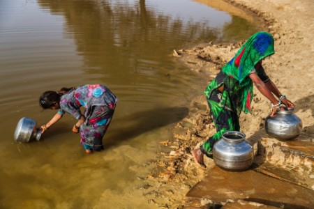 Girls collecting water lake desert village